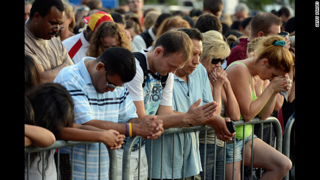 Mourners bow their heads in prayer during the vigil for the victims of the Aurora shooting.