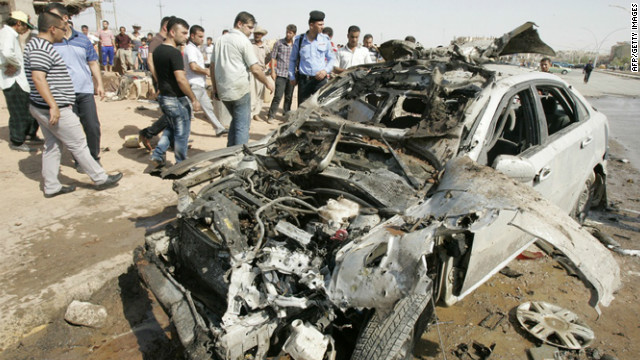 Iraqi police and pedestrians look at the shell of a car after a series of car bombs on July 23, 2012. 