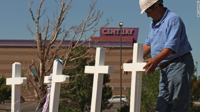 Greg Zanis places crosses at a makeshift memorial to victims of the Aurora, Colorado, movie theater shooting on Sunday, July 22. Zanis says he began building crosses to help comfort others after first creating one for himself as a memorial to his late father-in-law.
