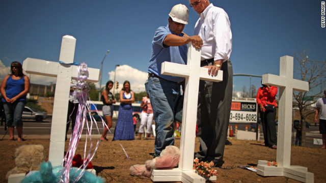 Zanis prays with Aurora Mayor Steve Hogan at the site of 12 crosses to remember those killed in the movie theater massacre.