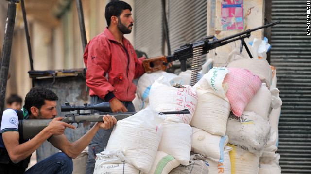 Syrian rebels take cover behind sandbags during fighting Monday at the entrance to the city of Selehattin.