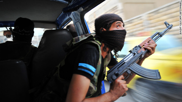 Syrian rebels hunt for snipers after attacking the municipality building in the city center of Selehattin on July 23.