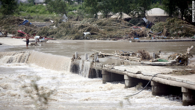 Water pours over a collapsed bridge leading to Laishui on Tuesday. The heavy rains have affected more than 6 million people in China.
