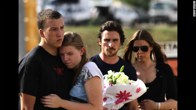 "A couple embraces as ""Dark Knight Rises"" star Christian Bale and his wife, Sandra Blazic, wait to place flowers at the memorial on Tuesday."