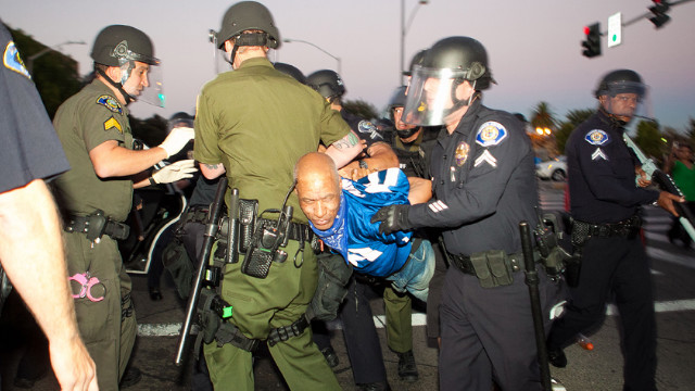 Police take a protester into custody.