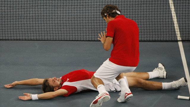 Wawrinka collapses after winning the match point in the final against Sweden's Simon Aspelin and Thomas Johansson.
