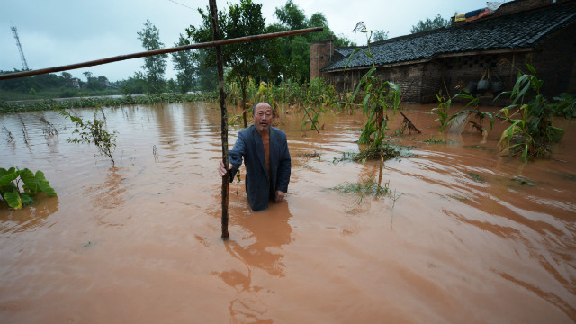 A farmer stands in his flooded field on the outskirts of Chongqing in southwest China on Sunday, July 22.
