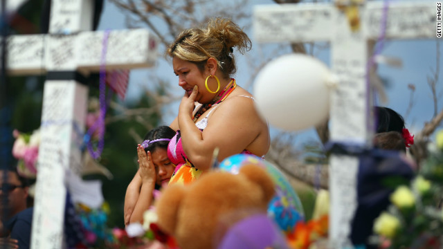 Angella Aquilis, left, and Maria Olivas mourn at a makeshift memorial across the street from the Century 16 movie theater.