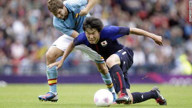 Spain's Inigo Martinez, left, fouls Kensuke Nagai of Japan during the match Thursday.