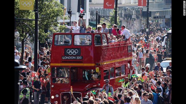 The Olympic torch is carried Thursday on top of an open top bus down Oxford Street in London.