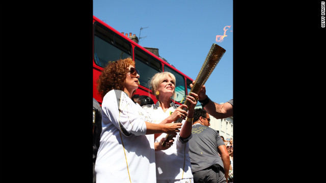 Torchbearers Jennifer Saunders and Joanna Lumley, known for their &quot;Absolutely Fabulous&quot; characters Edina and Patsy, carry the Olympic flame through Lambeth, Kensington and Chelsea on Thursday, July 26 in London. The flame is traveling 2,875 kilometers (1,786 miles) through the United Kingdom over 70 days. Its journey ends Friday at the opening ceremony of the London 2012 Olympic Games.