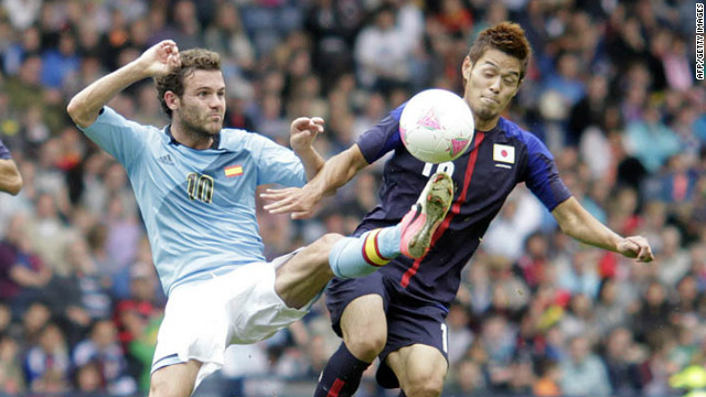 Spain's Juan Mata, left, challenges Hotaru Yamaguchi of Japan during a group D soccer match Thursday in Glasgow.