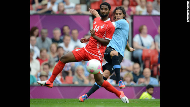Uruguay forward Edinson Cavani, right, slips a pass under United Arab Emirates defender Abdelaziz Sanqour, left, in Manchester on Thursday. Uruguay defeated the UAE, 2-1.