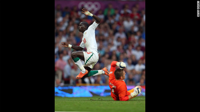 Sadio Mane of Senegal leaps over goalkeeper Jack Butland of Great Britain during the first-round men's soccer match between Great Britain and Senegal at Old Trafford on Thursday, July 26, in Manchester, England.