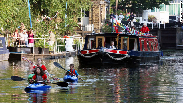 Torchbearer Paris Walker holds the Olympic flame Thursday as it travels on a barge at Camden Lock in London.