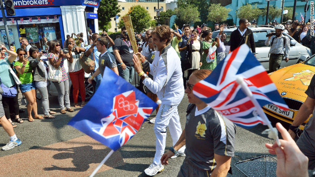 Indian Bollywood actor Amitabh Bachchan, center, carries the Olympic flame through the streets of London on Thursday, July 26, the day before the opening ceremony.