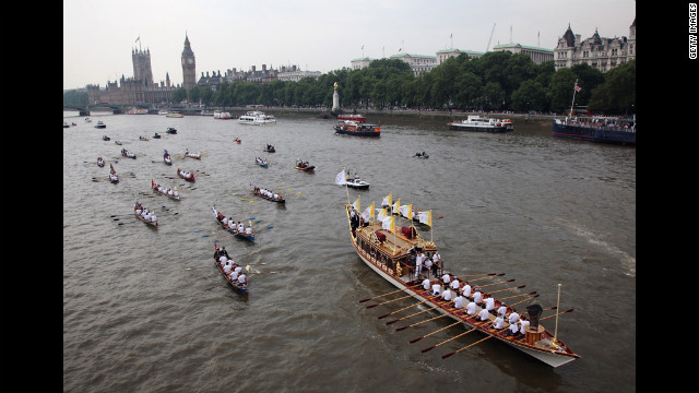 The Queen's royal row barge Gloriana carries the Olympic flame along the River Thames past the Parliament on Friday, July 27, the final day of the torch relay in London. 