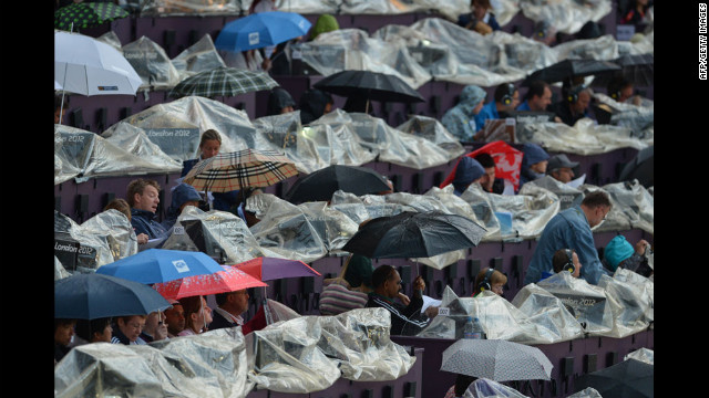 Spectators take shelter under umbrellas prior to the start of the opening ceremony.