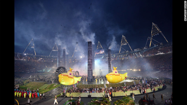 Inflatable yellow submarines float above artists during The Age of Industry scene.