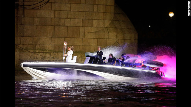 David Beckham passes under Tower Bridge driving a speedboat named &quot;Max Power,&quot; which carries the Olympic Torch.