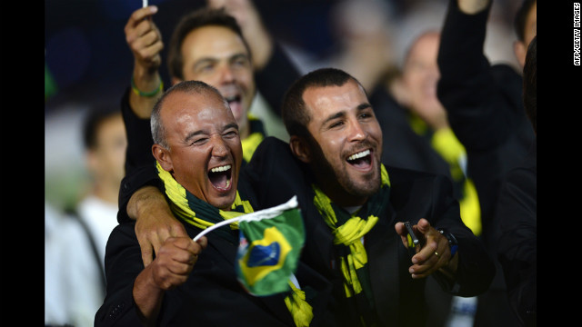 Members of Brazil's delegation hold their national flag as they walk during the opening ceremony.