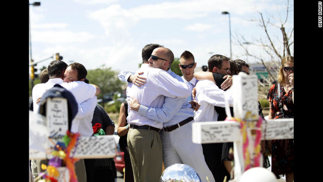 Members of Alex Sullivan's family embrace at a memorial across the street from the Century 16 movie theater on Thursday, July 26.