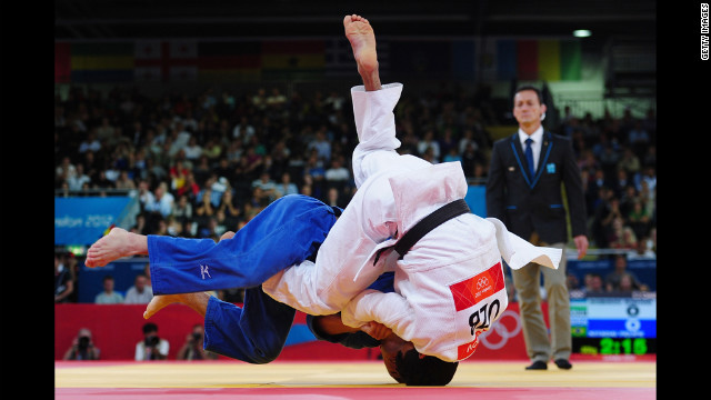 Felipe Kitadai of Brazil, in blue, competes with Rishod Sobirov of Uzbekistan in a judo match.