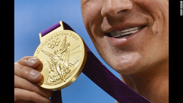 U.S. swimmer Ryan Lochte flashes his U.S. flag grill and the gold medal he won in the men's 400-meter individual medley.