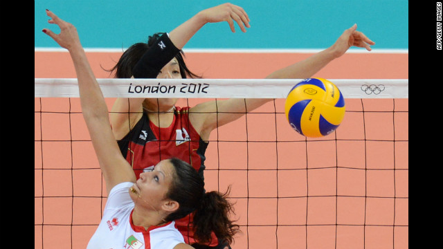 Algeria's Sehryne Hennaoui spikes the ball as Japan's Yukiko Ebata reaches to block during a women's volleyball match. 