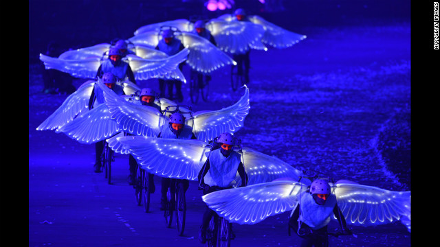 Artists wearing wings and riding bicylces perform during the ceremony.