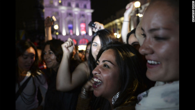 People cheer as they watch the opening ceremony on an outdoor screen at Piccadilly Circus.