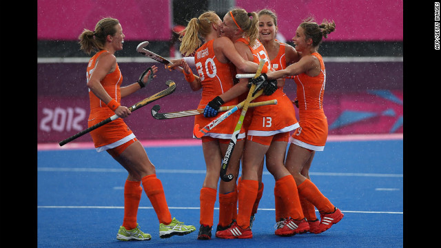 The Netherlands' women's field hockey team celebrates a third goal against Belgium.