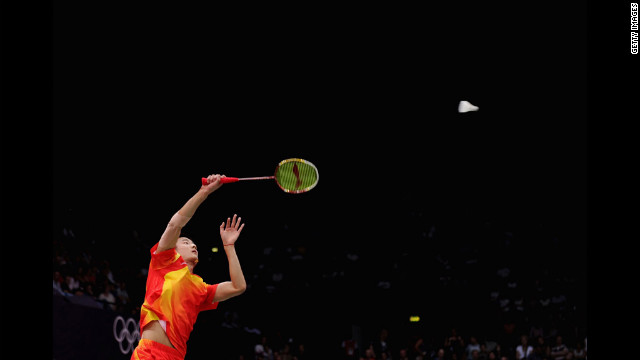 Long Chen of China returns a shot against Boonsak Ponsana of Thailand during the men's singles badminton match at Wembley Arena.
