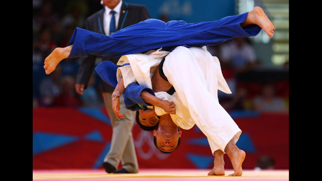 Masashi Ebinuma of Japan, in white, competes against Sergey Lim of Kazakhstan in a men's under 66-kilogram judo bout.