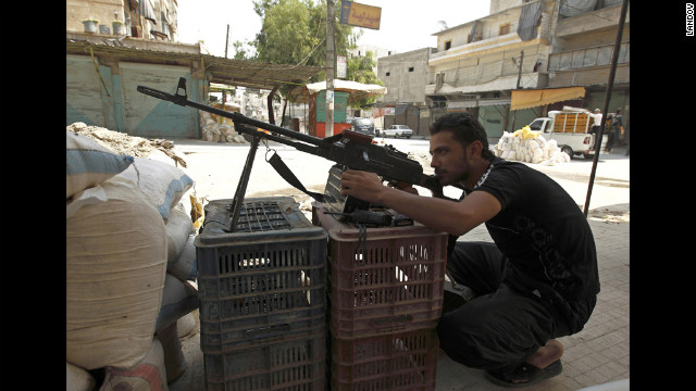 A Free Syrian Army fighter takes position Sunday, July 29, in Aleppo as people flee shelling. Intense clashes have been under way for more than a week between the regime and rebels in Aleppo, Syria's commercial and cultural center.