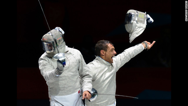 Italy's Diego Occhiuzzi, right, celebrates his victory over Romania's Rares Dumitrescu during the men's saber semifinal fencing bout.