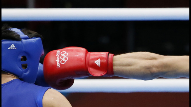 The fist of Turkey's Adem Kilicci lands against Nursahat Pazziyev of Turkmenistan during their first-round middleweight (75kg) bout.