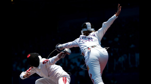 Sarra Besbes of Tunisia, left, tries for a point against Xiaojuan Luo of China during their women's epee fencing round Monday.