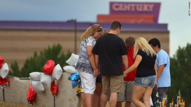 Visitors pray around a cross at the memorial across the street from the theater on Saturday, July 28.