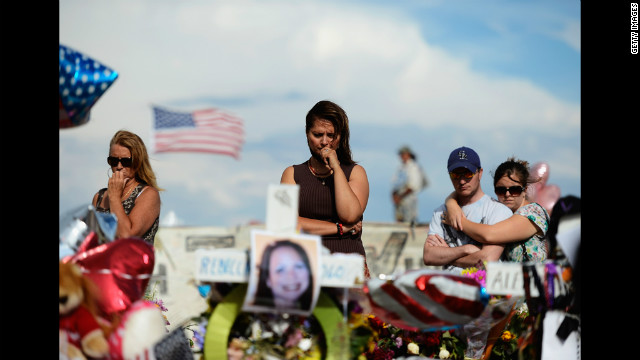 "Cynthia Davis, center, visits the roadside memorial set up for victims of the Colorado shooting massacre across the street from the Century 16 movie theater on Monday, July 30, in Aurora, Colorado. Twelve people were killed in the theater early July 20 during a screening of ""The Dark Knight Rises."" Suspect James Holmes was taken into custody shortly after the attack. <a href='http://www.cnn.com/2012/07/20/us/gallery/colorado-theater-shooting/index.html' target='_blank'>More photos: Colorado movie theater shooting</a>"