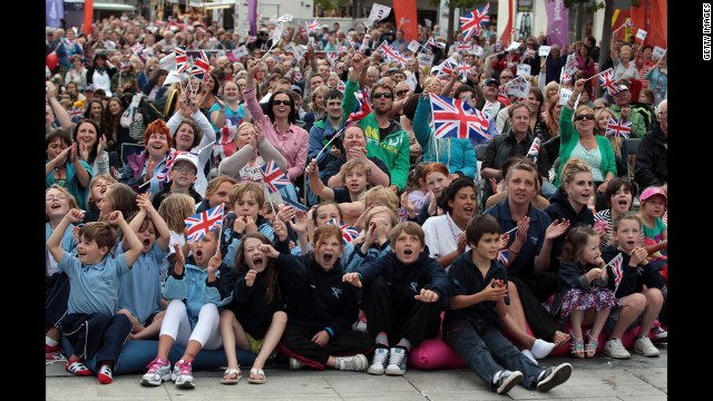 Great Britain supporters cheer as they watch diver Tom Daley on large screens erected in the city center of Plymouth, England on Monday.