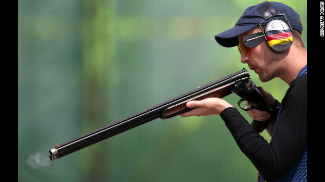 Germany's Ralf Buchheim blows in the barrel of his rifle as he competes in the men's skeet qualification on Monday.