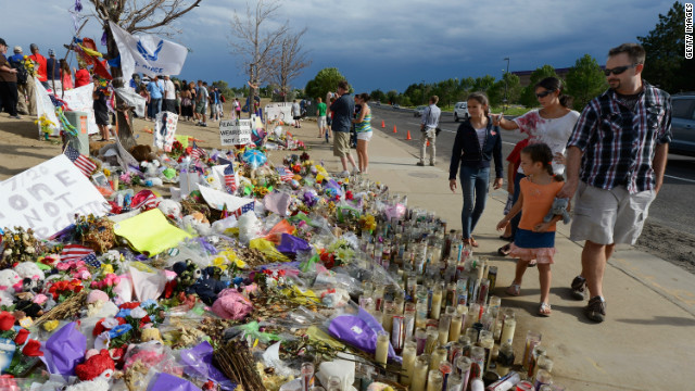 People continue to visit the roadside memorial set up for victims of the theater shooting massacre in Aurora, Colorado. 