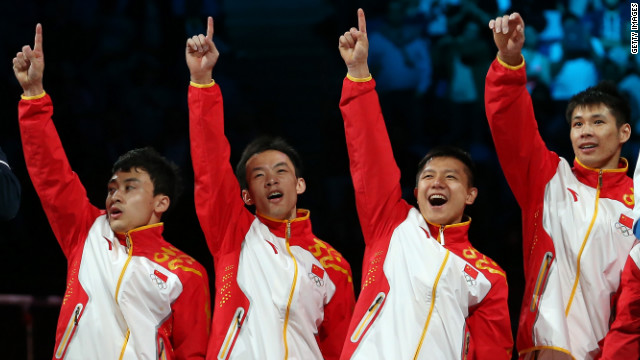 Gold medalists Zhe Feng, Weiyang Guo, Yibing Chen, Chenglong Zhang and Kai Zou of China celebrate on the podium during the medal ceremony in the artistic gymnastics men's team final.