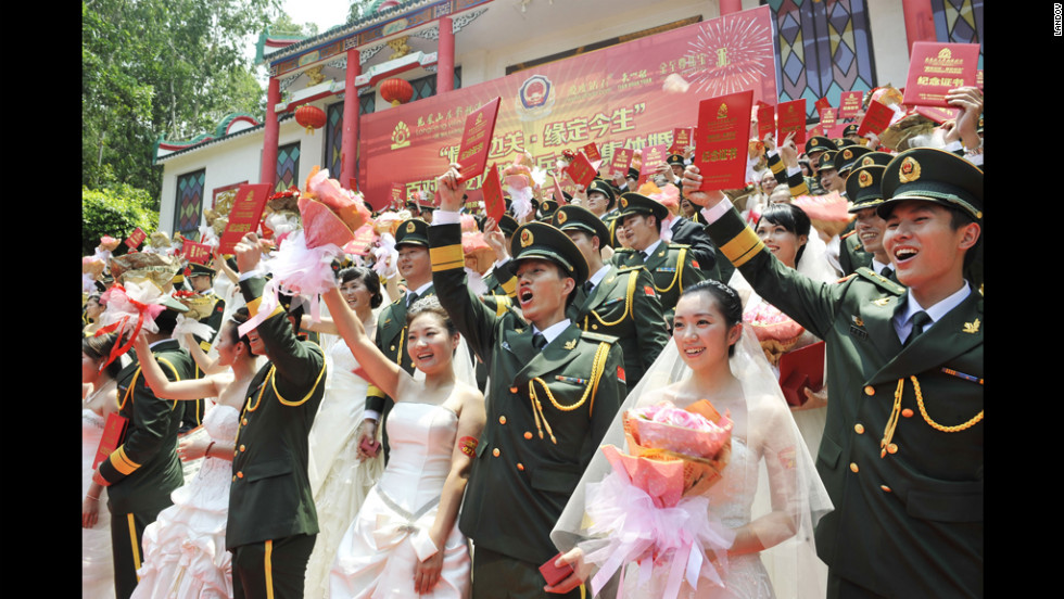 Couples pose for group photos during a group wedding ceremony for border police Monday in Dongguan, China. 
