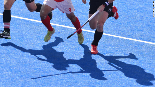 South Korea's Yung Sung Hoon dribbles past New Zealand defenders during the preliminary round men's field hockey match Monday.