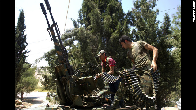 Rebel fighters load an anti-aircraft machine gun on an armored vehicle in Atareb, east of Syria's second-largest city, Aleppo, on Tuesday, July 31.