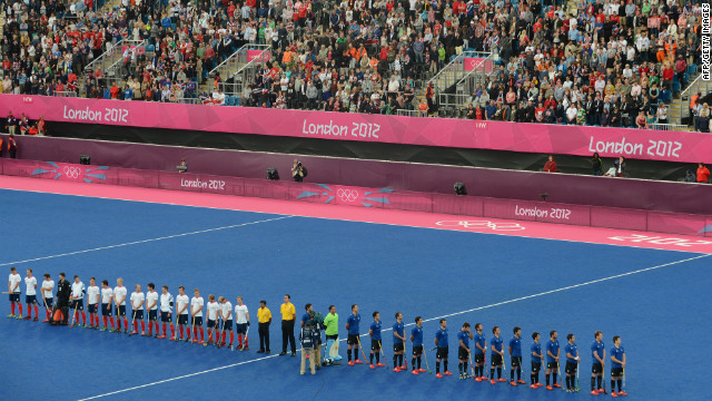 British and Argentinian team players line up at the start of the preliminary round men's field hockey match.