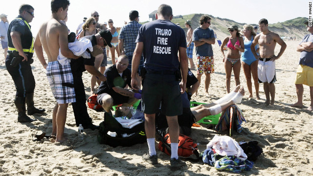 A man is treated for apparent shark bites on his legs Monday at Cape Cod's Ballston Beach.