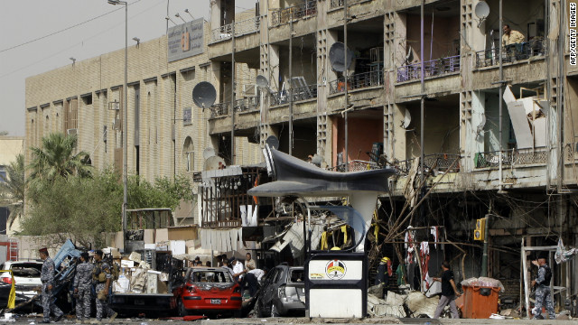 Iraqi security gather at the site of a twin car bombs in the Karrada area of the capital Baghdad on July 31, 2012.